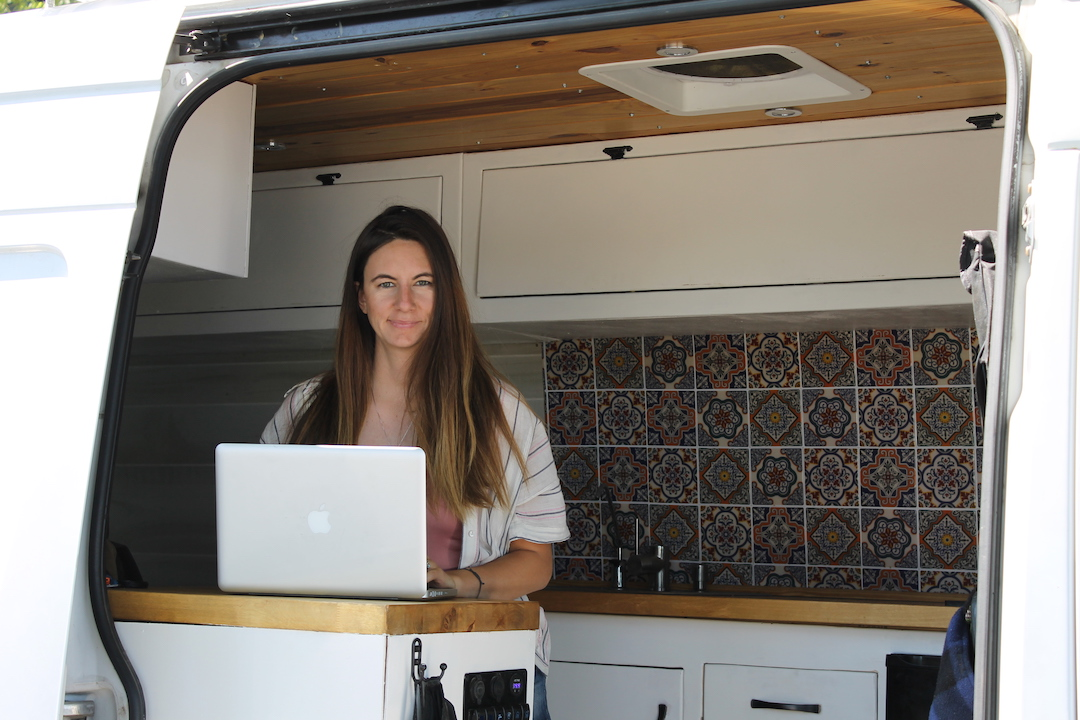 Woman in converted sprinter van:vanlife remote work